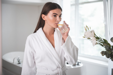 Portrait of orderly lady tasting appetizing mug of liquid while locating in wide apartment after taking bath