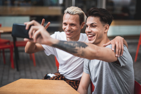 Portrait of beaming men taking selfie on phone while grimacing faces and gesticulating hands. They locating at desk outside