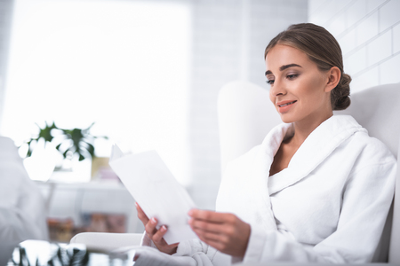 I am interested. Lovely young lady sitting on armchair and holding papers. She is wearing white soft bathrobe Banco de Imagens