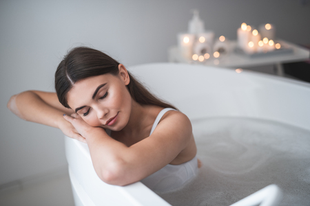 Portrait of calm woman with closing eyes enjoying during cosmetic procedure in contemporary bath. Candles locating opposite her. Pleased lady taking care of body during romantic atmosphere concept Stock Photo