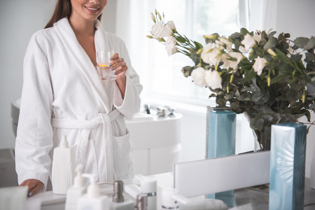 Outgoing lady tasting appetizing mug of liquid while looking at reflection in modern apartment. She wearing bathrobe
