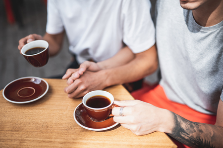 One guy holding hand of another man. They sitting at table and drinking cups of appetizing coffee