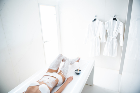 Do not disturb. Female well shaped body with cosmetic clay on legs and belly. Soft bathrobes hanging on the wall Stok Fotoğraf