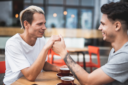 Side view positive male keeping arm of outgoing friend while speaking with him at desk. They tasting cups of liquid. Optimistic comrades having leisure together concept