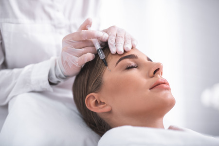 Beautician touching lady forehead and making injection under eyebrow