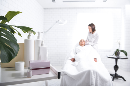 Young woman lying on daybed while doctor doing skincare procedure