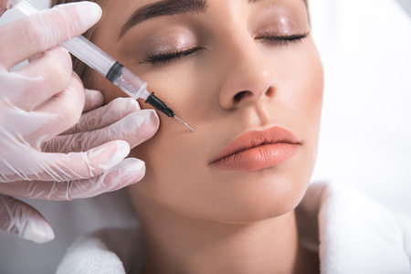 Close up portrait of cosmetologist hand in gloves holding syringe near young woman face. Stock Photo