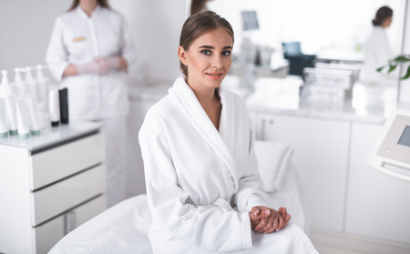 Lovely girl in soft bathrobe looking at camera with smile. Beautician in lab coat on blurred background 版權商用圖片