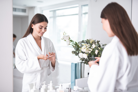 Portrait of happy woman keeping special liquid for taking care of skin on hands, while standing opposite mirror in bathrobe near flowers in white bright apartment Standard-Bild