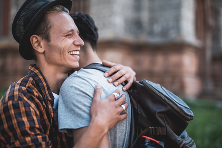 I am so glad to see you. Side view laughing guy embracing friend while meeting him on street Banco de Imagens