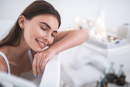 Portrait of satisfied woman with closing eyes resting during cosmetic procedure in bath opposite shelf with candles. She closing eyes during pleasure