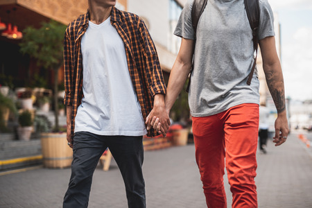 Close up male keeping arm of guy during walk. They moving together and gesticulating hands Stock Photo