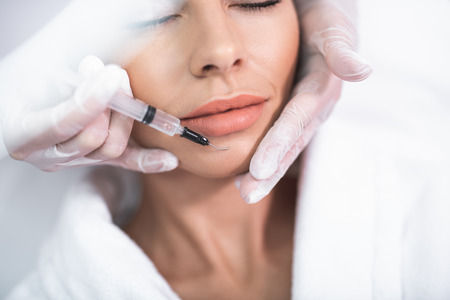Being careful. Close up portrait of beautiful lady with closed eyes and cosmetologist arms in gloves. Isolated on white