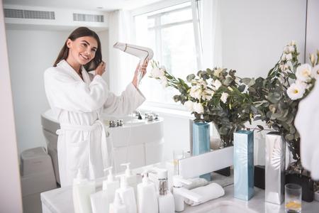 Retrato de mujer feliz que sopla el viento en el cabello después de tomar una ducha. Ella gesticula las manos mientras mira al espejo