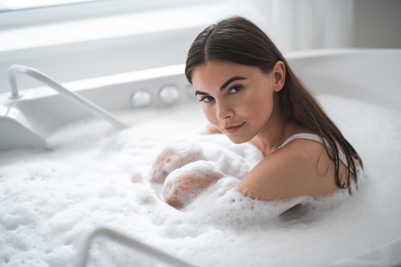 Portrait of serene girl looking at camera while having leisure in cozy bath. Orderly female during relaxing procedure concept