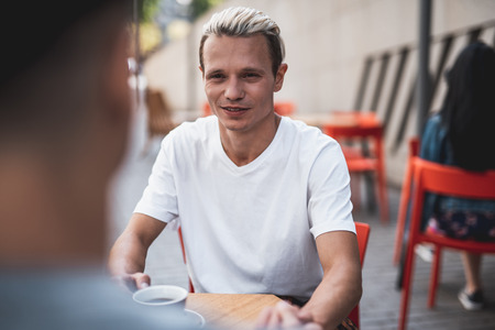 Portrait of cheerful male speaking with friend while tasting cup of coffee at desk. Communication of two comrades concept