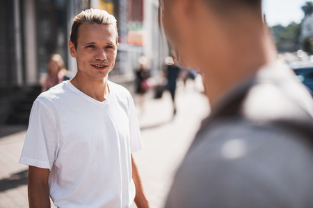 Portrait of optimistic man standing in street while talking with friend during sunny day in city
