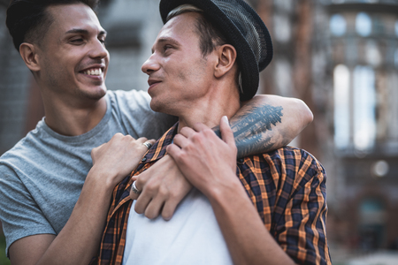 Side view optimistic male hugging outgoing friend while telling with him. They having fun outdoor