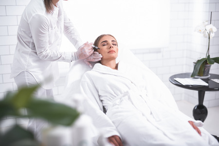 Gentle treatment. Serene young woman lying on daybed while beautician making injection