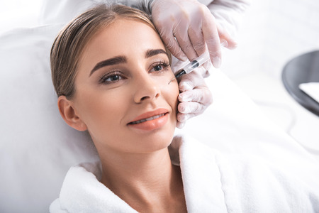 Relaxing in beauty salon. Close up portrait of attractive girl and cosmetologist hands in sterile gloves. Doctor carefully doing skincare procedure