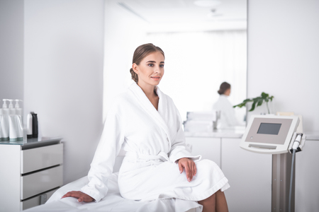 Lovely girl in soft bathrobe at beauty salon sitting on daybed. Beautician in lab coat standing near mirror