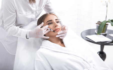Female beautician making injection to girl chin. She is wearing sterile gloves and using syringe Standard-Bild