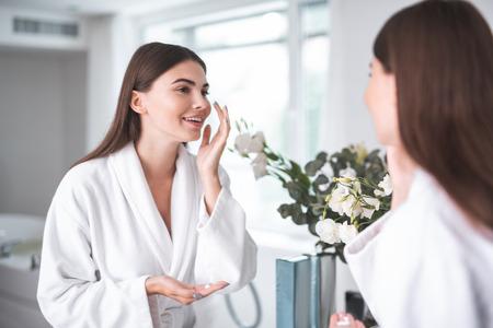 Retrato de dama positiva aplicando crema en la cara mientras mira el reflejo en el acogedor baño. Ella gesticula las manos. Concepto de procedimiento de tratamiento Foto de archivo