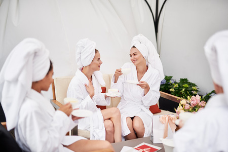 You make me laugh. Lovely young women with towels on heads holding cups of tea and smiling. They wearing soft white bathrobe