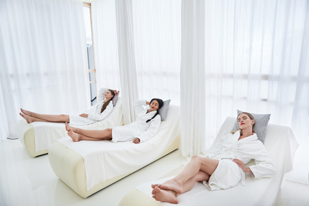 Beauty and healthcare. Charming young ladies with closed eyes lying on daybeds. They wearing white soft bathrobes 写真素材