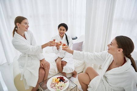 Happy event. Lovely young ladies in bathrobes holding glasses of champagne with strawberry. Women sitting on daybeds and toasting