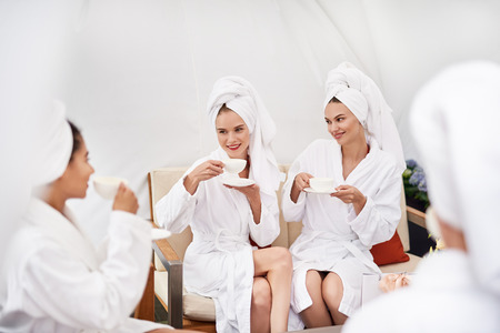 Glad to be here. Cheerful young women with towels on heads holding cups with hot drinks and smiling. They wearing soft bathrobes and sitting on couch 写真素材