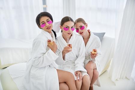 Pasar tiempo en el spa. Sonrientes señoritas con máscaras en los párpados inferiores sentados en el diván. Llevaban albornoces y copas de champán