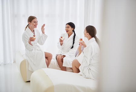 I am bride. Smiling young lady in bathrobe demonstrating ring to happy friends. Women holding glasses of champagne with strawberry and sitting on daybeds Stock Photo