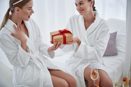I am touched. Smiling young woman giving gift box with red ribbon to happy lady. They sitting on daybed at spa salon