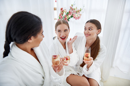 Can you believe this. Young women in bathrobes holding glasses of champagne and listening friend Foto de archivo - 107354453