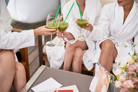 Good mood. Glasses of green cocktails with drinking straws in ladies hands. Women sitting at the table in spa lounge Stok Fotoğraf - 107354662