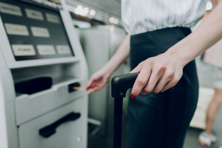 Close up of female hand is holding suitcase, while inserting bank card into cash dispenser