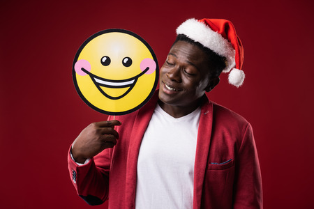 Good mood. Handsome male in santa hat holding yellow carton icon of smiling face. Isolated on red background