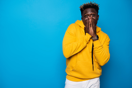 Feeling a little shy. Waist up portrait of young man in yellow hoodie covering nose and lips with arms. Isolated on blue background