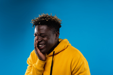 Funny moment. Portrait of young male with closed eyes chuckling at something. He is wearing yellow hoodie and standing on blue background