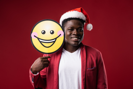 How do i look. Handsome man in santa hat comparing facial expression with carton icon of smiling face. Isolated on red background