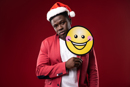 Cheer up. Handsome man in santa hat posing with emoji icon. Isolated on red background Фото со стока