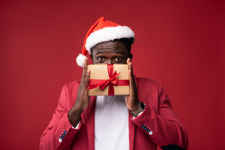 Look what i got. Young man in santa hat covering lower face with gift box. He is looking at camera with wide opened eyes and raised eyebrows