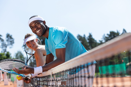 Focus on happy guy preparing for double match on sunny day. He is standing with woman and leaning against net while holding rackets and ball. They are both enjoying team game with friend Foto de archivo