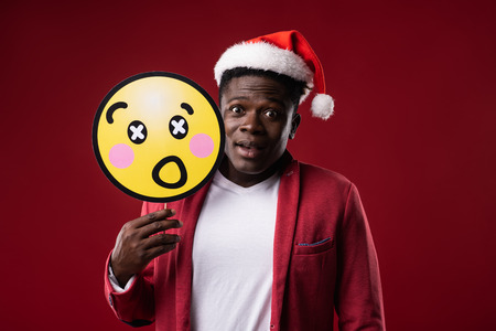 Unexpected news. Handsome man in santa hat repeating expression of shocked face on carton icon. Isolated on red background