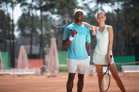 Full length portrait of smiling man and woman during tennis match. They are standing close and holding rackets while lady is putting arm on male shoulder with affection. Copy space in left side