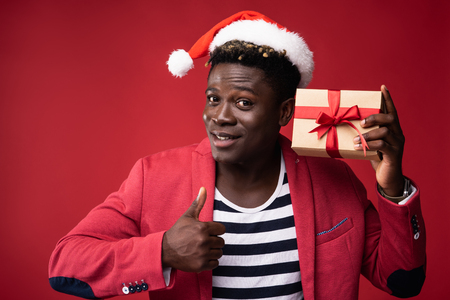I like it. Portrait of cheerful male in santa hat demonstrating present and doing thumbs up gesture. Isolated on red background