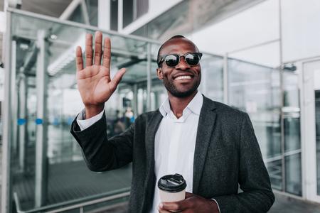 Hola hombre. Cintura para arriba retrato de empresario está de pie cerca de la entrada y saluda a alguien con la mano Foto de archivo