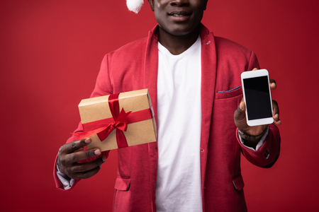 Good stuff. Smiling guy in santa hat holding gift box with ribbon and mobile phone. Isolated on red background