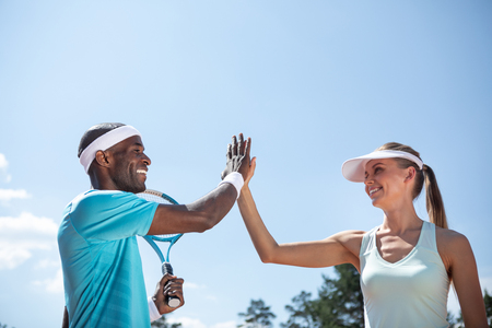 Low angle of positive couple playing tennis outdoor on warm sunny day. They are high-fiving while celebrating victory after tennis match. Athletes are standing beside while guy is holding racket Imagens